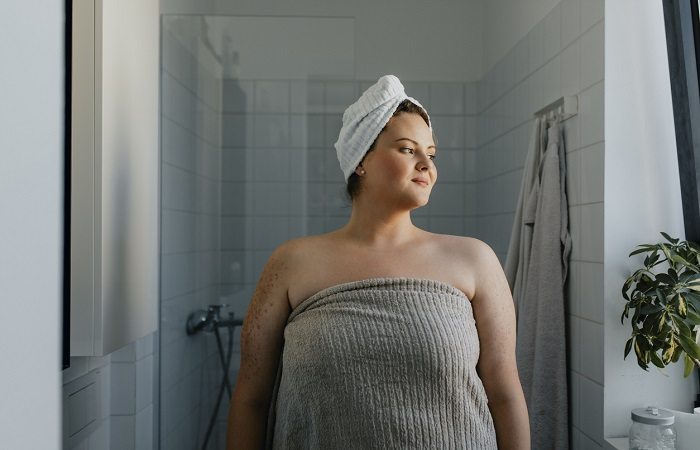 Portrait of a Happy Overweight Woman Standing in the Bathroom after a Relaxing Shower