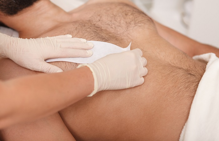 Man getting waxing hair removal at the salon